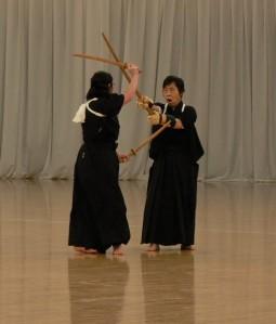 Tendo Ryu en el Kobudo Taikai 2010(C) Jeff Broderick naginatajutsu, koryu, doble kodachi contra jo. Los kata que se realizan con naginata y espada corta reflejan con sumo realismo las limitaciones de un arma tan larga en distancia corta. La practicante (o el practicante) que maneja la naginata la arroja al suelo y desenvaina con rapidez el kodachi para acabar con su oponente cuando este acorta la distancia y la naginata se vuelve ineficaz. El origen de estas técnicas es doble: por un lado la lucha cuerpo a cuerpo, en la que se empleaban armas pequeñas; y por otro la defensa femenina, consistente en clavar una daga (kaiken) a un adversario que pretendiese usar su superioridad física o técnica  en el combate a corta distancia.